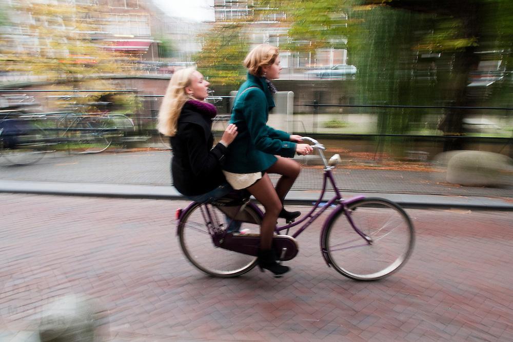 In Utrecht fietst een meisje met een ander meisje achterop de bagagedrager van de fiets over de Oudegracht.<br /> <br /> In Utrecht a girl cycles with another girl on the back of the bike at the Oudegracht.