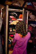 Sadma Khan, 19, looks through a cabinet in her mother's one-room house they share with her entire immediate family in a slum area of Tonk, Rajasthan, India, on 19th June 2012. She was married at 17 years old to Waseem Khan, also underaged at the time of their wedding. The couple have an 18 month old baby and Sadma is now 3 months pregnant with her 2nd child and plans to use contraceptives after this pregnancy. She lives with her mother since Waseem works in another district and she can't take care of her children on her own. Photo by Suzanne Lee for Save The Children UK