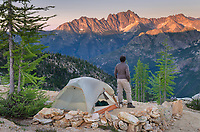 Adult male standing next to backpacking tent and gazing at view of Silver star Mountain on ridge above Cutthroat Pass, near Pacific Crest trail. North Cascades Washington