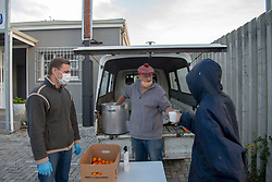 """(L to R) Chris Dicks, board member, and Andy Loughton, chairman of Thomas House of Hope, serve breakfast outside the premises in Somerset West, Western Cape, on Tuesday morning, May 5, 2020. Thomas House normally provides programs through which people living on the streets can work in exchange for tokens that they can use for meals, ID books, clothing, toiletries and showers. But during lockdown, the centre has had to suspend its activities to simply serve meals to those who are hungry. Loughton, who also runs a bakery business, says things are uncertain. """"Everything is unsettled right now. ... When we go back to work, it's going to be a bit like starting the business all over again,"""" he says. The same thing is true at the centre, he adds. Loughton says he doesn't know how or where some of the """"normal"""" client base is right now. PHOTO: EVA-LOTTA JANSSON"""