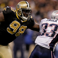 2009 November 30: New Orleans Saints defensive tackle Sedrick Ellis (98) reaches for New England Patriots running back Kevin Faulk (33) during a 38-17 win by the New Orleans Saints over the New England Patriots at the Louisiana Superdome in New Orleans, Louisiana.
