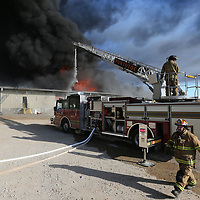 Firefighters try and contain a fire at American Furniture Friday morning in Ecru. The fire jumped two fire walls and destroyed much of the facility.