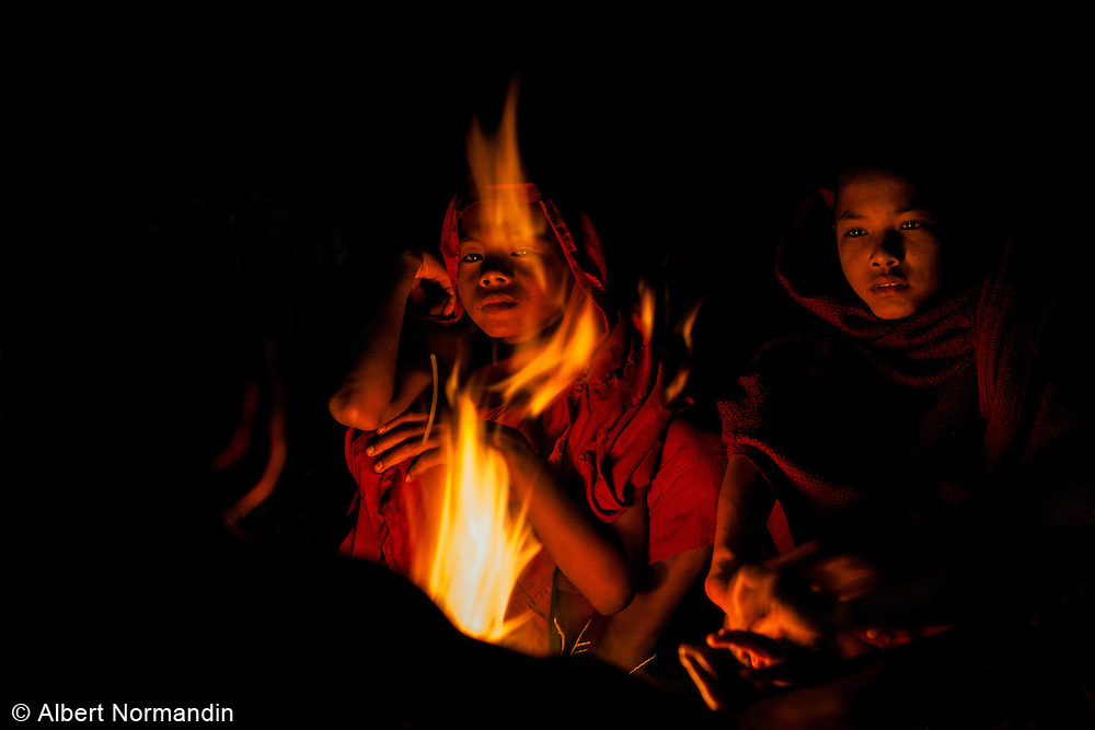 Young Novice Monks try to stay warm around camp fire at Ananda Temple Festival