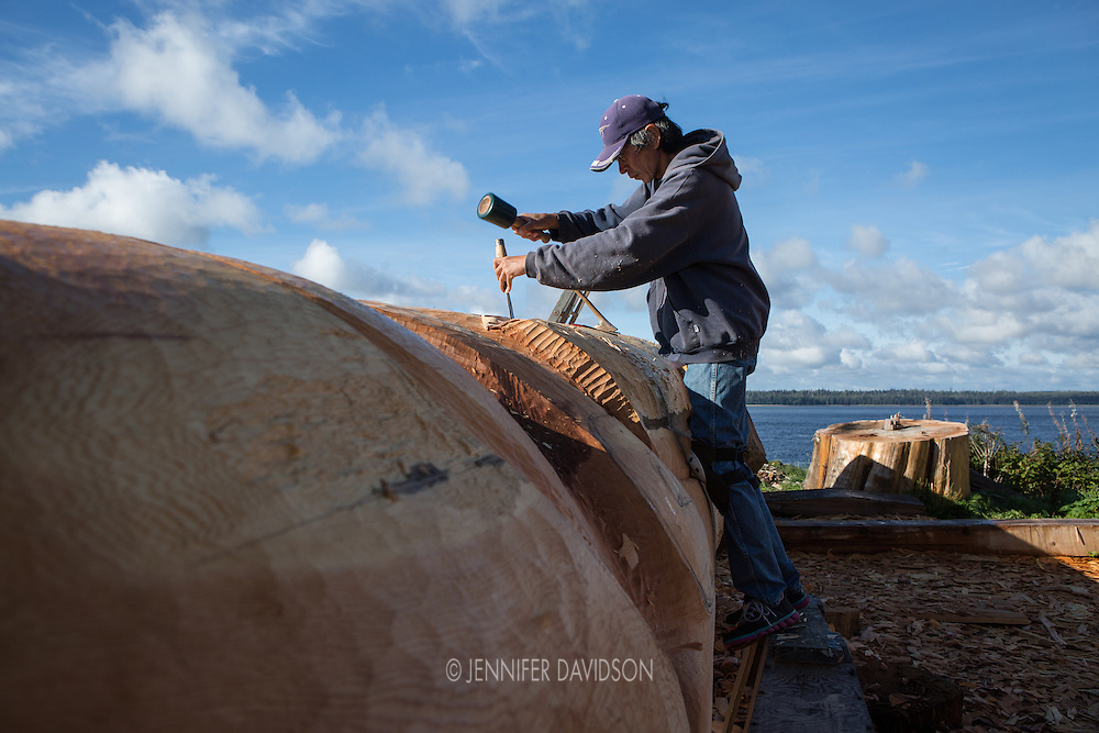 Haida totem carver Leon Ridley carves a totem pole designed by artist Jim Hart outside his studio in Old Masset, Haida Gwaii.