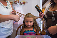 Angela and Crystal Jarrell prep JayCee, 3, for the Coal Festival beauty pageant. The annual Coal Festival celebrates the history and heritage of coal mining in southern West Virginia. (Photo by Lauren Schneiderman)