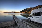 Luxury campervan beside still and mirror like Lake Tarawera, Rotorua, New Zealand