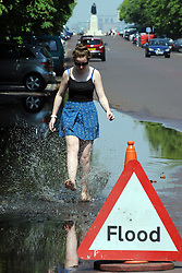 &copy; Licensed to London News Pictures. 18/07/2014<br /> Teenager,  Sarah Mary (age 15) from Bromley cooling off in the flood water from  last nights storms in Greenwich Park,Greenwich,London today (18.07.2014)<br /> People enjoying the heatwave weather at Greenwich Park,Greenwich,London.<br /> (Byline:Grant Falvey/LNP)