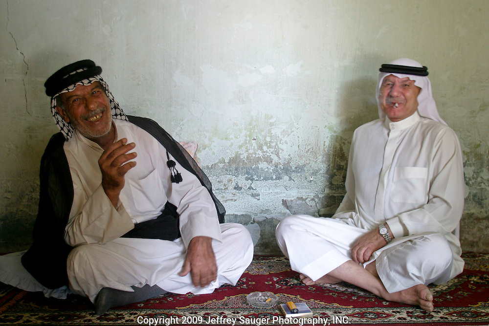 Malik Al-kasid, right, laughs with his cousin Askendar Faris, left, as he receives male relatives at his sister Batoul Al-kasid's home in Nasiriyah. The men were gathering for the caravan to Al-kasid's Istikbal in his home village Soug Al-Sheuk on the outskirts of Nasiriyah, Iraq, Tuesday, July 29, 2003. The Al-kasid family fled Iraq after the Gulf War and their part in the uprising against Saddam Hussein in 1991, spent 3 years in Rafha, Saudi Arabia and finally settled in Dearborn, MI.The family hasn't been home to Iraq in 13 years.