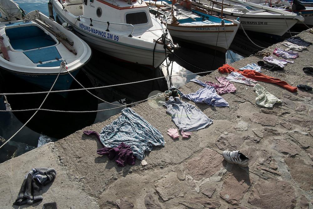 GRIECHENLAND, Lesbos, Mithymna/Molivos, 28.10.2015 / Im Hafen von Mithymna: Kleidung liegt zum Trocknen am Kai aus. In der Nacht zuvor kam es zu einem schweren Bootsunglueck vor der Kueste. Rettungskraefte konnten mindestens 242 Menschen retten, waehrend elf Menschen nur noch tot gebogen werden konnten. Die Kuestenwache geht davon aus, dass die Zahl der Toten noch deutlich steigen wird.