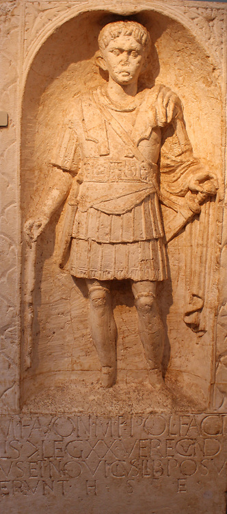 Tombstone of centurion M Favonius Facilis from Colchester, AD 43-50.  He wears the full armour of a Roman officer and carries a centurion's vine- rod (vitis).  He served at Camulodunum (modern Colchester), and the inscription records that the monument was set up by two of his ex-slaves, called Verecundus and Novicius.  One of the earliest dated sculptures from Roman Britain.