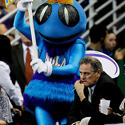 April 15, 2012; New Orleans, LA, USA; New Orleans Hornets mascot Hugo walks past New Orleans Saints general manager Mickey Loomis during the second half of a game against the Memphis Grizzlies at the New Orleans Arena. The Hornets defeated the Grizzlies 88-75.  Mandatory Credit: Derick E. Hingle-US PRESSWIRE