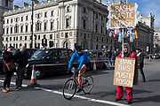 On the occasion of Commonwealth Day, a cyclist pedals past an environmental activist standing in Parliament Square, advocating the ban on plastics around the world, on 11th March 2019, in Westminster, London, England.