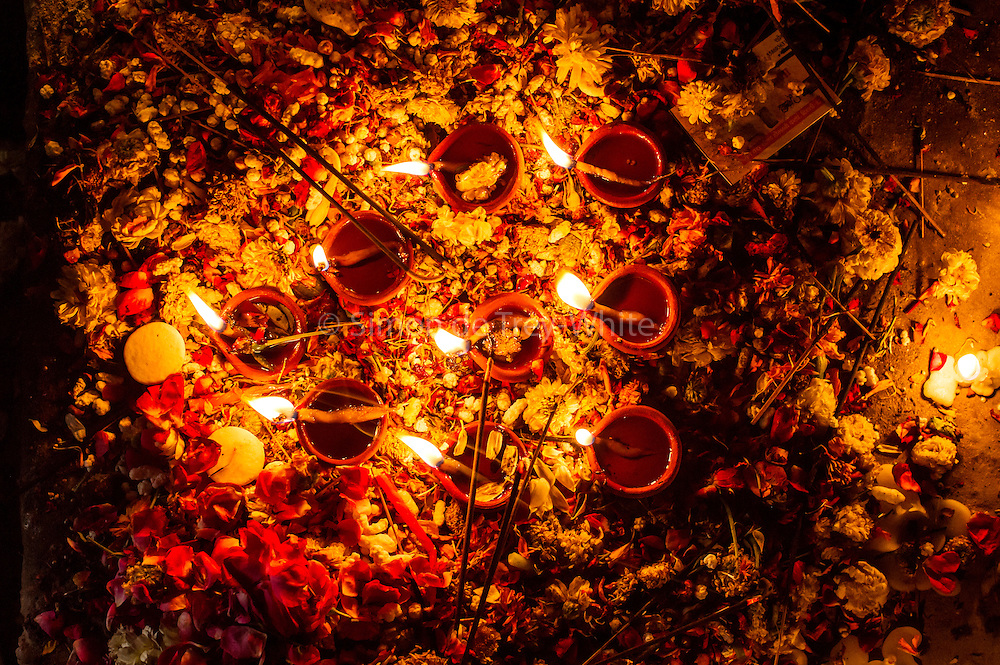 23rd April 2015, New Delhi, India. Oil lamps and incense sticks burn at a shrine dedicated to Djinn worship in the ruins of Feroz Shah Kotla in New Delhi, India on the 23rd April 2015<br /> <br /> PHOTOGRAPH BY AND COPYRIGHT OF SIMON DE TREY-WHITE a photographer in delhi<br /> + 91 98103 99809. Email: simon@simondetreywhite.com<br /> <br /> People have been coming to Firoz Shah Kotla to leave written notes and offerings for Djinns in the hopes of getting wishes granted since the late 1970's. Jinn, jann or djinn are supernatural creatures in Islamic mythology as well as pre-Islamic Arabian mythology. They are mentioned frequently in the Quran  and other Islamic texts and inhabit an unseen world called Djinnestan. In Islamic theology jinn are said to be creatures with free will, made from smokeless fire by Allah as humans were made of clay, among other things. According to the Quran, jinn have free will, and Iblīs abused this freedom in front of Allah by refusing to bow to Adam when Allah ordered angels and jinn to do so. For disobeying Allah, Iblīs was expelled from Paradise and called &quot;Shayṭān&quot; (Satan).They are usually invisible to humans, but humans do appear clearly to jinn, as they can possess them. Like humans, jinn will also be judged on the Day of Judgment and will be sent to Paradise or Hell according to their deeds. Feroz Shah Tughlaq (r. 1351&ndash;88), the Sultan of Delhi, established the fortified city of Ferozabad in 1354, as the new capital of the Delhi Sultanate, and included in it the site of the present Feroz Shah Kotla. Kotla literally means fortress or citadel.