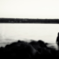 The silhouette of a young child standing beside a lake