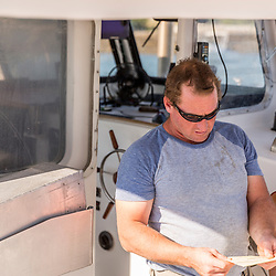 Captain Ivan Bly aboard his lobster boat 'Iris-Irene' at the Tenants Harbor Fisherman's Coop in Tenants Harbor, Maine.