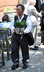Rena Brannan helps to bring out flowers from St.Paul's Church in Covent Garden, London, after a memorial service for the actor Simon Ward who is the father of her partner the actress Sophie Ward , Tuesday, 9th July 2013<br /> Picture by Stephen Lock / i-Images