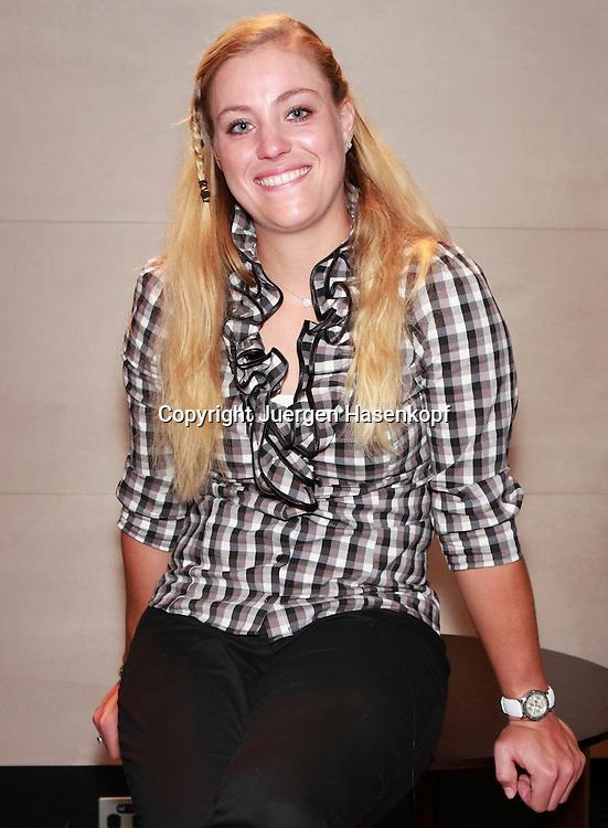 Tennis,Fed Cup Spielerin Angelique Kerber (GER) sitzt auf einer Tischkante,.Einzelbild,Halbkoerper,Hochformat,Portrait,laechelt,freundlich,