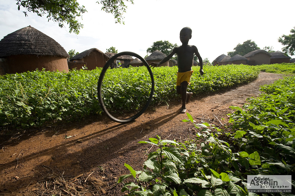 A child plays with a bicycle tire in the village of Ying, northern Ghana, on Monday June 4, 2007..