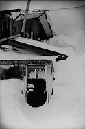 Snow is again drifting in front door of a farmhouse where snow is deeper than the second floor.  Harukaizawa village in the mountains of Aomori Prefecture.   Japan
