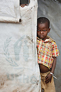 A boy stands in the doorway of a temporary shelter made from UNHCR-provided tarp at the Miketo IDP settlement, Katanga province, Democratic Republic of Congo on Sunday February 19, 2012.