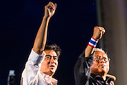 "15 NOVEMBER 2013 - BANGKOK, THAILAND:  Former Thai Prime Minister ABHISIT VEJJAJIVA and SUTHEP THAUGSUBAN, leader of anti-government protests and the former Deputy Prime Minister of Thailand, stand on the stage at Democracy Monument during an anti-government protest in Bangkok. Tens of thousands of Thais packed the area around Democracy Monument in the old part of Bangkok Friday night to protest against efforts by the ruling Pheu Thai party to pass an amnesty bill that could lead to the return of former Prime Minister Thaksin Shinawatra. Suthep announced an all-out drive to eradicate the ""Thaksin regime."" The protest Friday was the biggest since the amnesty bill issue percolated back into the public consciousness. The anti-government protesters have vowed to continue their protests even though the Thai Senate voted down the bill, thus killing it for at least six months.    PHOTO BY JACK KURTZ"
