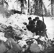 Forestry workers sitting by fire making a hot drink in snow covered forest, Finland, 1959