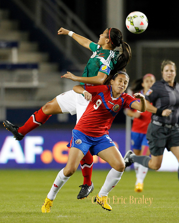 Mexico's Lydia Nayeli Rangel (7) heads the ball over Costa Rica's Carolina Venegas (9) during the first half of a CONCACAF Women's Championship soccer match, Thursday, Oct. 16, 2014, in Kansas City, Kan. (AP Photo/Colin E. Braley)