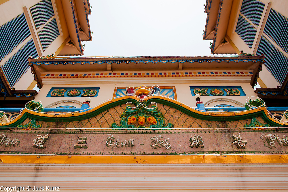 "29 MARCH 2012 - TAY NINH, VIETNAM:   The front of the main worship hall at the Cao Dai Holy See in Tay Ninh, Vietnam. Cao Dai (also Caodaiism) is a syncretistic, monotheistic religion, officially established in the city of Tây Ninh, southern Vietnam in 1926. Cao means ""high"" and ""Dai"" means ""dais"" (as in a platform or altar raised above the surrounding level to give prominence to the person on it). Estimates of Cao Dai adherents in Vietnam vary, but most sources give two to three million, but there may be up to six million. An additional 30,000 Vietnamese exiles, in the United States, Europe, and Australia are Cao Dai followers. During the Vietnam's wars from 1945-1975, members of Cao Dai were active in political and military struggles, both against French colonial forces and Prime Minister Ngo Dinh Diem of South Vietnam. Their opposition to the communist forces until 1975 was a factor in their repression after the fall of Saigon in 1975, when the incoming communist government proscribed the practice of Cao Dai. In 1997, the Cao Dai was granted legal recognition. Cao Dai's pantheon of saints includes such diverse figures as the Buddha, Confucius, Jesus Christ, Muhammad, Pericles, Julius Caesar, Joan of Arc, Victor Hugo, and the Chinese revolutionary leader Sun Yat-sen. These are honored at Cao Dai temples, along with ancestors.    PHOTO BY JACK KURTZ"