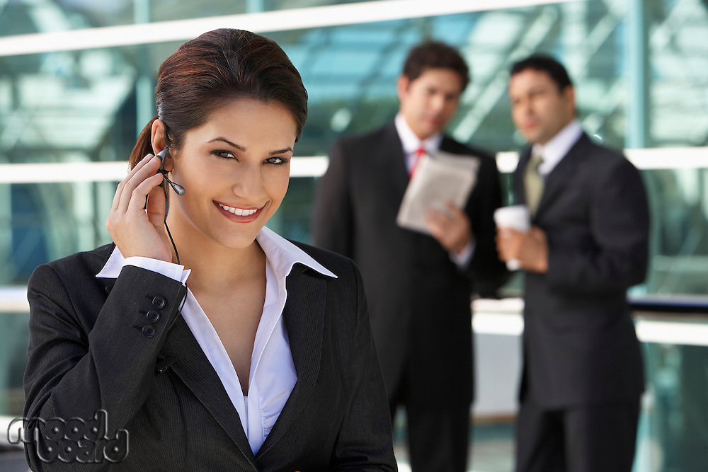 Businesswoman using earpiece with businessmen in background