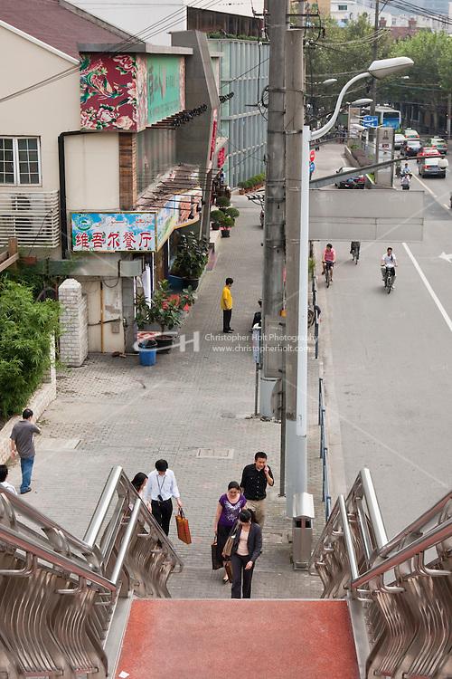People climb up stairs on pedestrian bridge Shanghai China
