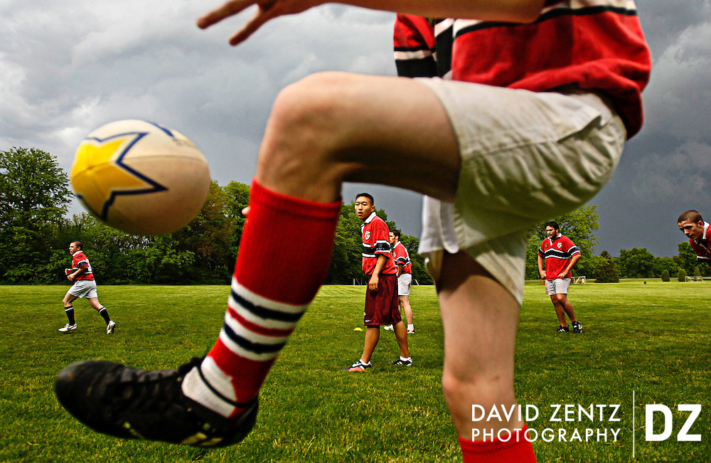 Richard Kim is seen through the legs of TJ Lane as the new high school rugby club started by Mike Schubach, president of the Peoria Rugby Club practice at Detweiller Park Wednesday evening.