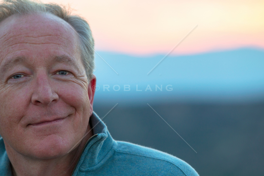 portrait of a handsome middle aged man with blue eyes outdoors