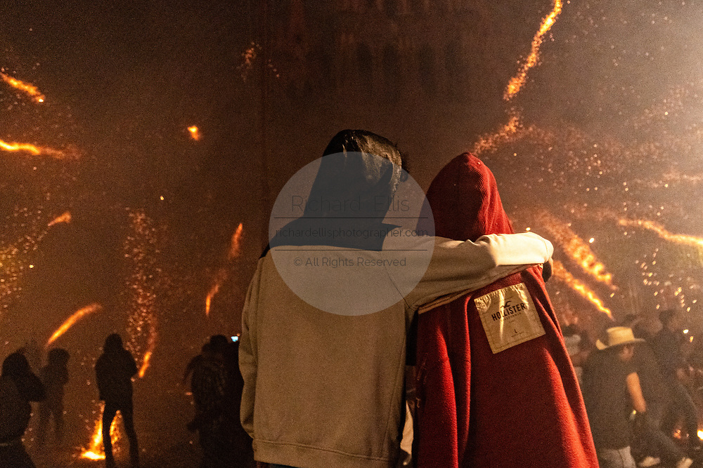 A couple watches as dozens of sky rockets explode around them during the Alborada festival September 29, 2018 in San Miguel de Allende, Mexico. The unusual festival celebrates the cities patron saint with a two hour-long firework battle at 4am representing the struggle between Saint Michael and Lucifer.