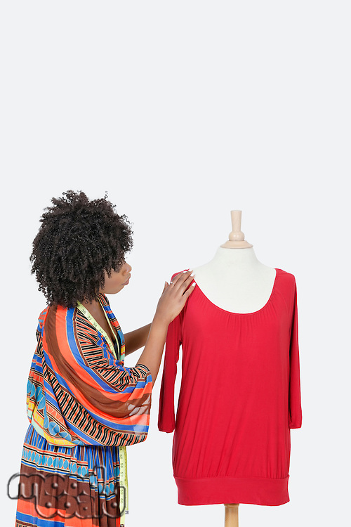 African American female fashion designer looking at red tunic over gray background