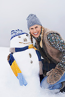 Woman kneeling by snowman on snow-covered hill