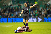 Referee Kevin Clancy gives a foul, as Arnaud Djoum (#10) of Heart of Midlothian lies injured during the Ladbrokes Scottish Premiership match between Hibernian FC and Heart of Midlothian FC at Easter Road Stadium, Edinburgh, Scotland on 29 December 2018.