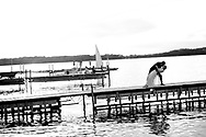 A couple dips on a pier on Lake Mendota at Memorial Union on their wedding day in May 2014.