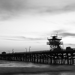 Orange County California San Clemente pier at sunset black and white panorama photo. Orange County is part of Southern California in the Western United States of America. Panoramic photo ratio is 1:3. Copyright ⓒ 2017 Paul Velgos with All Rights Reserved.