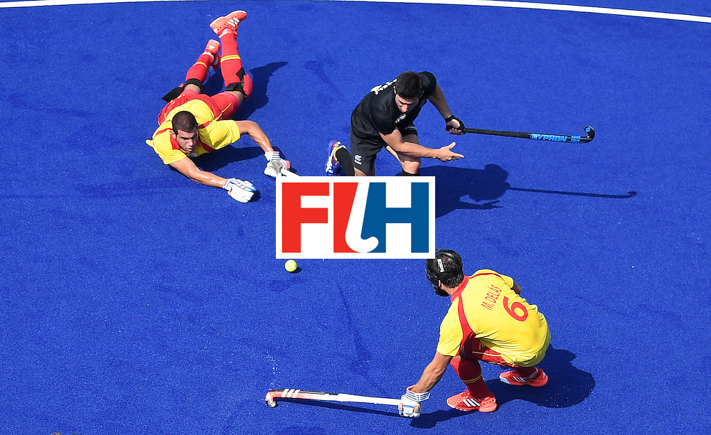New Zealand's Kane Russell (C) tries to get past Spain's Miguel Delas (bottom) during the men's field hockey New Zealand vs Spain match of the Rio 2016 Olympics Games at the Olympic Hockey Centre in Rio de Janeiro on August, 9 2016. / AFP / MANAN VATSYAYANA        (Photo credit should read MANAN VATSYAYANA/AFP/Getty Images)