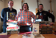 Left to right: Matthew Becker, Justin King and Chris Meier pose with their table top games before choosing which one to play first.  It's a regular ritual for the three long-time friends.  They bring a selection of games, argue about what they want to play, then open a box and begin rolling dice or setting up pieces.  December 7, 2013.  Photo by Andrew Welsch/NYCity Photo Wire