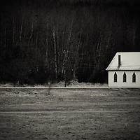 A little white church sitting in the woods looking deserted.