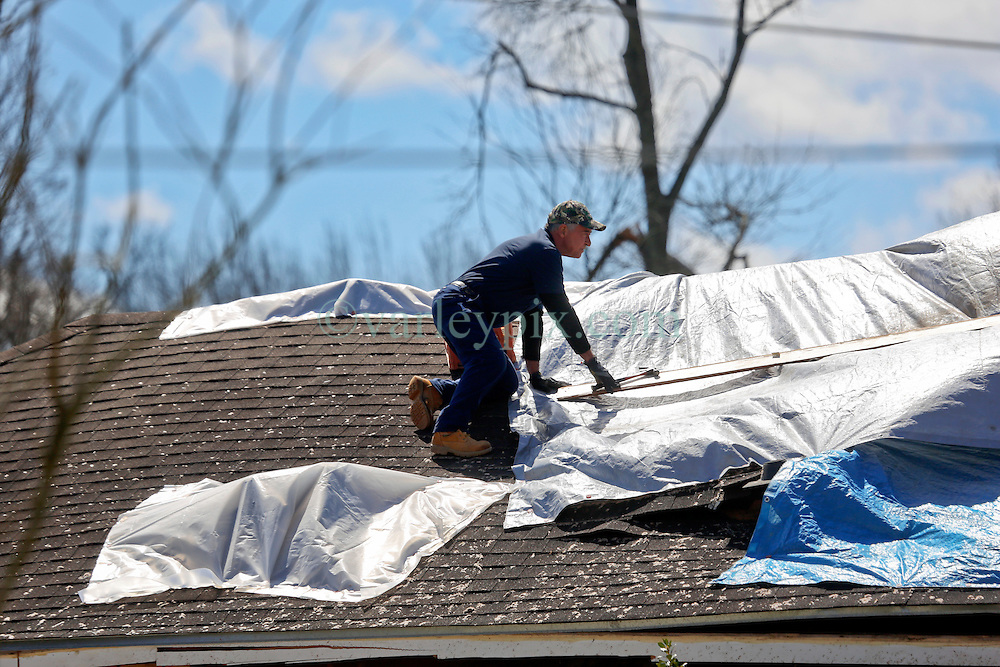 24 February 2016. Schexnaydre St, Convent, Louisiana.<br /> Scenes of devastation following a deadly EF2 tornado touchdown. 2 confirmed dead. A resident clambers onto his roof to patch holes left by the storm with blue tarp.<br /> Photo©; Charlie Varley/varleypix.com