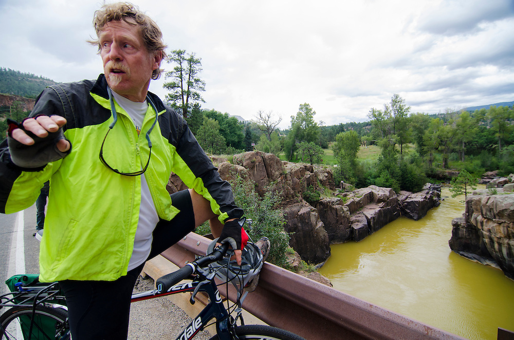 """Jimbo"" Buickerood, Public Lands Coordinator for San Juan Citizens Alliance, takes a moment from his bike ride to check up on the progression of toxic wastewater contaminating the Animas River, as it makes its way south towards Durango, Colorado."