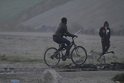 October 25, 2016 - Calais, Nord-Pas-de-Calais-Picardie, France - A refugee cycles on the outskirt of the Jungle. A little less than 2000 refugees are expected to be disbursed from the Jungle to different areas in France on the 2nd day of the eviction of the Jungle in Calais. It is also expected that the demolition of the camp will start. (Credit Image: © Michael Debets/Pacific Press via ZUMA Wire)