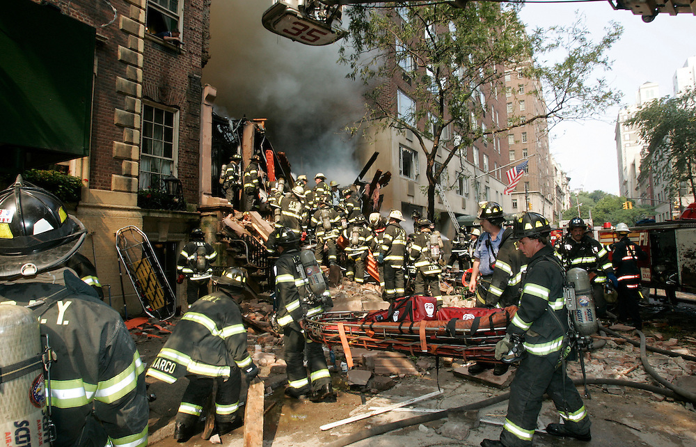 Fire fighters work the scene of an explosion that caused the collapse of a two story building in New York, July 10, 2006.