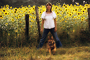 Cindy Wright and dog, in front of a field of sunflowers on a cattle farm managed by Peter Menzel in rural Charlotte, Tennessee. Tennessee. Sunflower plants.  MODEL RELEASED. USA.