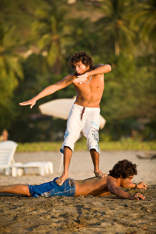 A surfer stans on his friend on the beach pretending that his friend i a surf board. His friend looks resigned