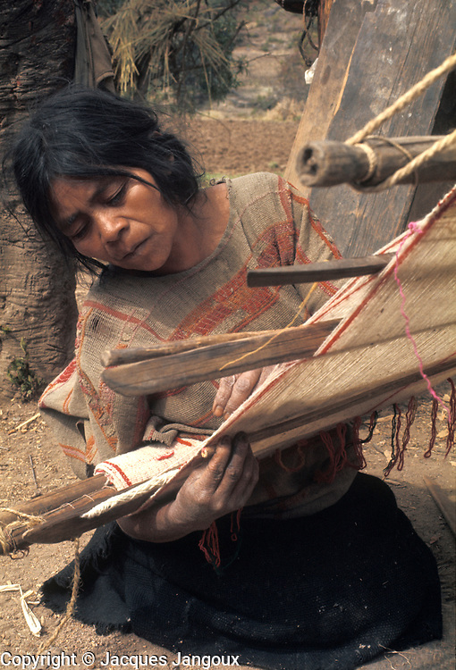 Mexico Oaxaca State Mixtec Indian woman weaving using backstrap loom.