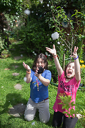© Licensed to London News Pictures . 29/06/2013 . London , UK . Natasha Campo (12) and Manuela Campo (10) play with toy snow in the sunshine in Finchley , North London today (Saturday 29th June)  . Photo credit : Joel Goodman/LNP
