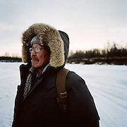 """I was just out jigging for pikes. Nothing today. I was fishing on the Kuskokwim [River]. It's right on the other side of this river (Tuluksak River) about a mile away. I walk everyday about four to five miles a day. I go down here, I go down river, about an hour and a half walk. I like walking. People come by on snow machines and offer me a ride home and I say, 'no, I will walk home.' It's a little different this year—only a little bit of snow, and last year we got nothing. There should be more snow. I have been fishing on the Kuskokwim River almost every year of my life. Most of my catch I give away to dog mushers in town. The Kuskokwim 300 [Dog Sled Race] is going to be pretty soon."" — Tommy Owen is Yup'ik and lives in Tuluksak, Alaska."